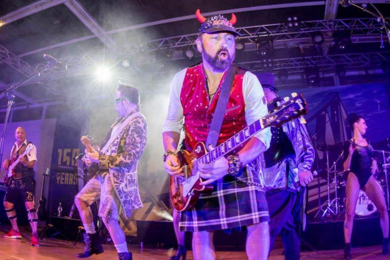Mitglied der Oktoberfestband München mit Gitarre und Schottenrock